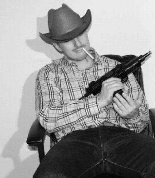 A man sits in a chair holding a gun, with a cigarette in his mouth