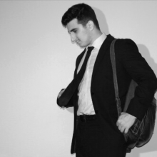 A man dressed in a suit and tie, carrying a leather backpack