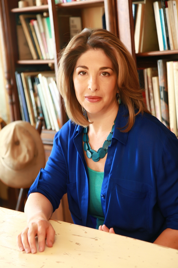 Headshot of Naomi Klein sitting in a desk in front of a bookshelf