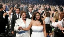 Two women dressed in white walk down after being married during the Mass Ceremony at the 56th Grammy Awards