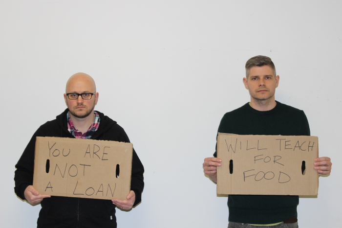 """Eric Lohman and Warren Steele holding up signs that say """"You are not a loan"""" and """"will teach for food"""""""